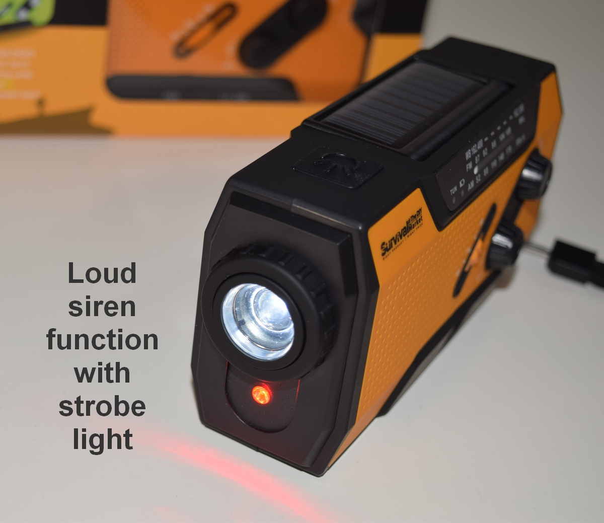 The survival radio includes a bright flashlight and a flashing red alarm light with loud siren function